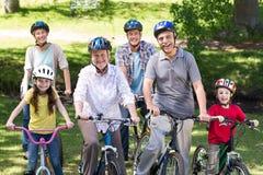 Família feliz em sua bicicleta no parque fotografia de stock