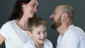 A família feliz em t-shirt brancos idênticos abraça-se próximo acima no estúdio na sessão fotográfica filme