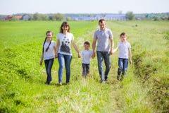 Família feliz em um campo Fotos de Stock Royalty Free