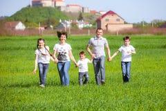 Família feliz em um campo Fotografia de Stock