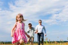 Família feliz em um prado no verão Fotos de Stock Royalty Free