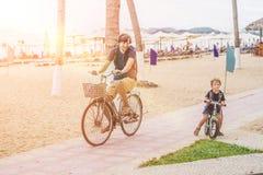 A família feliz está montando bicicletas fora e sorriso Pai em um b Imagens de Stock