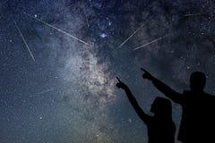 A família feliz está olhando o chuveiro de meteoro Nigh céu imagens de stock