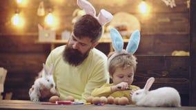 A família feliz está preparando-se para a Páscoa Orelhas vestindo do coelho do menino bonito da criança pequena O homem e um meni