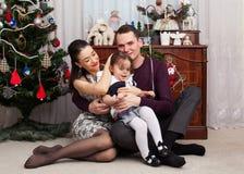 A família feliz está sentando-se contra a árvore de Natal imagens de stock royalty free