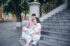 A família feliz está sentando-se nas escadas com um menino louro pequeno em seus joelhos do ` s da mãe Imagem com foco seletivo e Fotografia de Stock