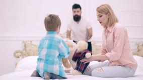 A família feliz está tendo o divertimento no quarto A mãe, o pai e o filho com brinquedo do luxuoso plaing na cama O menino fe