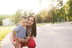 Família feliz exterior, menino que corre fora de sua mãe Imagem de Stock Royalty Free