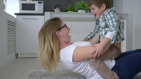 Família feliz, fêmea com a criança que tem o divertimento que encontra-se no assoalho em casa vídeos de arquivo