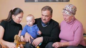A família feliz grande com um bebê suas mãe e avós tem o divertimento em casa no sofá Riem e falam entre vídeos de arquivo