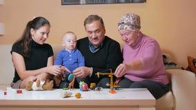 A família feliz grande com um bebê suas mãe e avós tem o divertimento em casa no sofá Riem e falam entre video estoque