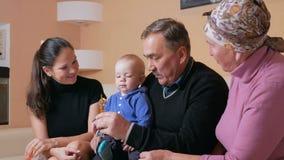 A família feliz grande com um bebê suas mãe e avós tem o divertimento em casa no sofá Riem e falam entre filme