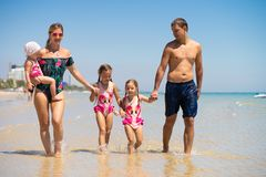 A família feliz grande está tendo o divertimento na praia conceito de uma grande família no mar Encalhe a forma imagem de stock royalty free