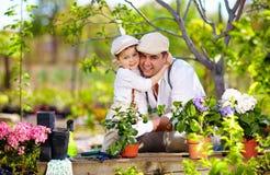 A família feliz importa-se com plantas no jardim da mola Fotos de Stock
