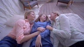 Família feliz, irmãs engraçadas com queda da mamã na cama durante a menina do riso e das cócegas do divertimento