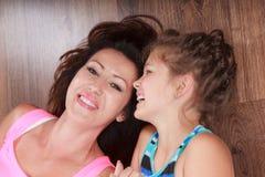 Família feliz Mãe e criança que encontram-se no assoalho home Fotos de Stock
