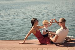 Família feliz Mãe e pai que fazem o gesto do coração ou do amor com mãos perto de sua criança A família feliz passa o tempo fotografia de stock royalty free