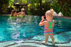 Família feliz - a mãe, filha, filho tem o divertimento na piscina fotos de stock