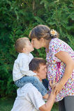 Família feliz Mãe grávida com seus marido e filho no parque O Mum beija o filho e o paizinho que beija mums incha-se Foto de Stock