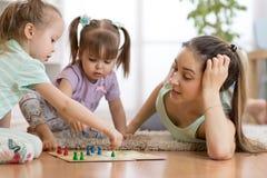 Família feliz Mãe nova que joga o boardgame de Ludo com suas filhas ao passar o tempo junto em casa fotos de stock royalty free