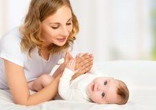 Família feliz. mãe que joga com seu bebê na cama fotos de stock royalty free