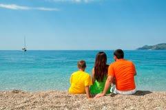 Família feliz: Mamã, paizinho e filho sentando-se na praia, Imagem de Stock Royalty Free