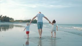 Família feliz mostrada em silhueta que joga e que tem o divertimento na praia no por do sol Movimento lento Liberdade feliz da in video estoque