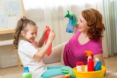 Família feliz - a mulher e sua filha pequena bonito estão tendo o divertimento, usando um pulverizador e um pano ao limpar sua ca imagem de stock royalty free