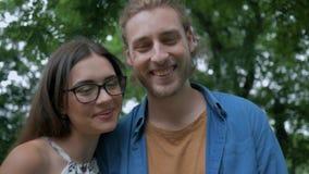 Família feliz, mum de sorriso de óculos com o paizinho que olha pouca filha e que abraça fora filme