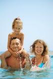 Família feliz na associação. Espirrando a água. imagem de stock