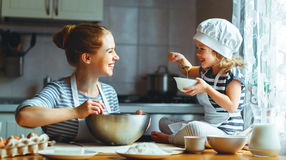 Família feliz na cozinha a mãe e a criança que preparam a massa, cozem Fotos de Stock