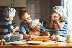 Família feliz na cozinha mãe e crianças que preparam a massa, vagabundos Fotografia de Stock Royalty Free