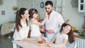 A família feliz na cozinha, a mamã, o paizinho e as filhas comem morangos, movimento lento video estoque