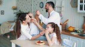 A família feliz na cozinha, a mamã, o paizinho e as filhas comem morangos, movimento lento