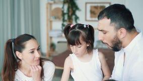 A família feliz na cozinha, a mamã, o paizinho e as filhas comem morangos, movimento lento vídeos de arquivo
