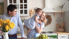 A família feliz na cozinha, onde a mãe guarda sua filha, e no paizinho está estando próximo vídeos de arquivo