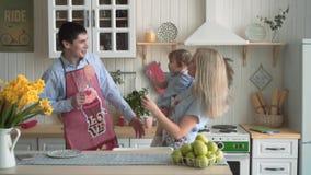 Fam?lia feliz na cozinha, onde a mam? est? guardando sua filha A mam? e o paizinho cantam em microfones imagin?rios e em dan filme