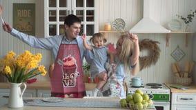 Fam?lia feliz na cozinha, onde a mam? est? guardando sua filha A mam? e o paizinho cantam em microfones imagin?rios e em dan?a filme