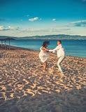 Família feliz na dança da praia na areia imagem de stock