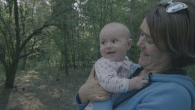 Família feliz na floresta - a mãe beija seu bebê no movimento lento filme
