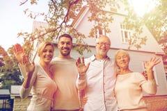 Família feliz na frente da casa fora imagens de stock royalty free