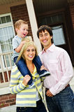 Família feliz na frente da HOME imagem de stock