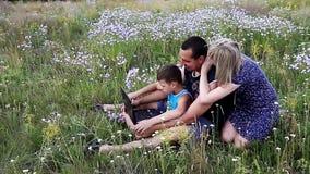 Família feliz na natureza com computador filme