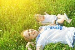 Família feliz na natureza a filha da mamã e do bebê está jogando no Fotografia de Stock