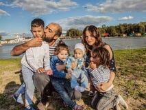Família feliz na natureza no fundo de um lago bonito Filhas do paizinho dois da mamã e dois filhos fotografia de stock royalty free