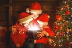 Família feliz na Noite de Natal a mãe e as crianças descobrem um miliampère fotografia de stock royalty free