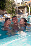 Família feliz na piscina fotografia de stock royalty free