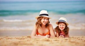 Família feliz na praia abraço da filha da mãe e da criança no mar imagem de stock royalty free
