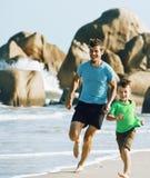 Família feliz na praia que joga, pai com a costa de mar de passeio do filho foto de stock