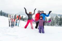 Família feliz na roupa do inverno na estância de esqui - esqui, inverno, neve, divertimento - mamã e filhas que apreciam férias d imagem de stock